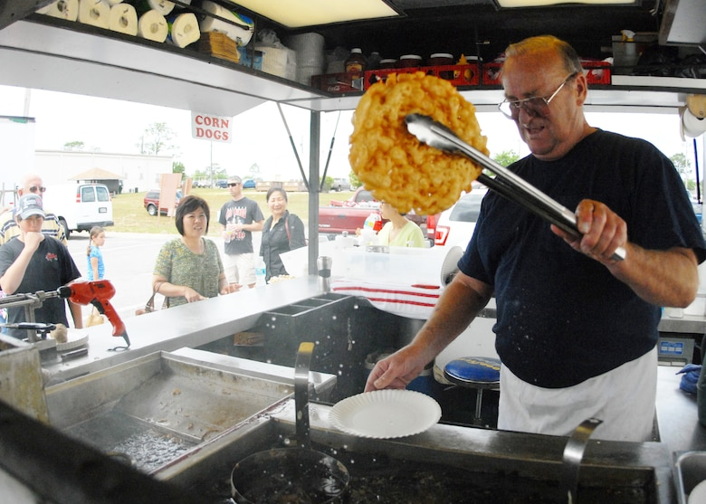 Ted Roberts, a 28-year Air Force veteran, dries a newly created funnel cake before adding a topping at his refreshment stand during the case lot sale held at Duke Field May 2. The retired lieutenant colonel sold refreshments and snacks to customers waiting to go into the warehouse.  The Fort Walton Beach native said that after he retired, his wife told him 'he wasn't going to play golf all day – he had to get a job.'  He has been running the refreshment stand ever since.  U.S. Air Force photo/Staff Sgt. Samuel King Jr.