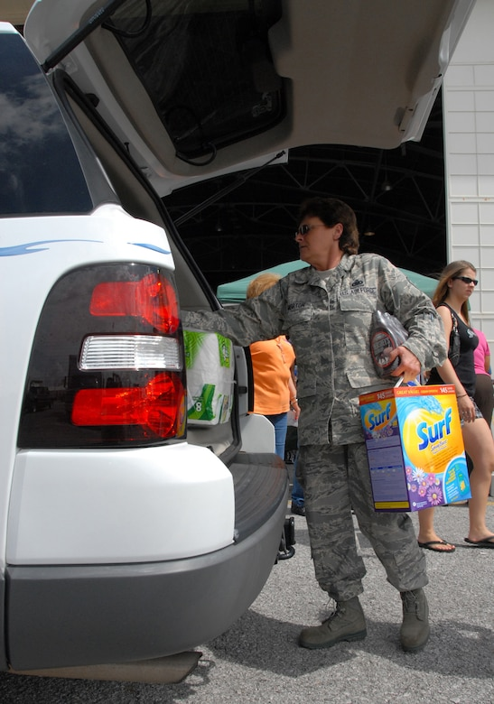 Senior Master Sgt. Theresa Morton, 919th Logistics Readiness Squadron, helps customers load up their cars after checking out at the case lot sale at Duke Field May 2.  People began lining up early, braved the heat of the day, and long wait to get the deals available from the sale.  U.S. Air Force photo/Staff Sgt. Samuel King Jr.
