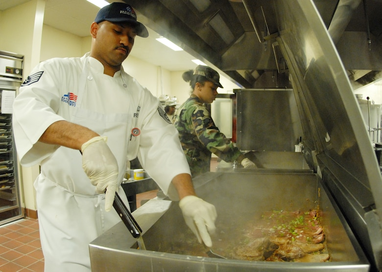 Staff Sgt. Chito Reyes, 919th Services Flight, flips pork chops while Senior Airman Brittnie Lewis stirs another vat in preparation for the lunch May 3 at the Duke Field dining facility.  The 919th SVF won a Hennessy Award this year for their superior performance at the dining facility.  U.S. Air Force photo/Staff Sgt. Samuel King Jr.