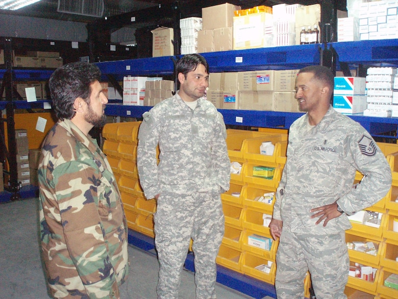 Master Sgt. Dewane Brown, Medical Embedded Training Team mentor, discusses medical logistics operations with Sgt Zia, Afghan National Army regional hospital warehouse worker, with Sergeant Brown's interpreter, Mr. Doust Mohammad. Sergeant Brown is helping modernize the Afghan healthcare system by bringing modern medicine, technology, and supply operations to Afghanistan. A previous healthcare system was virtually non-existent under the Taliban regime. (Courtesy photo)
