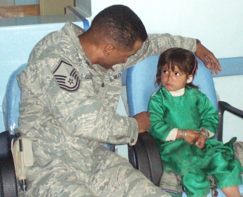 Master Sgt. Dewane Brown, Medical Embedded Training Team mentor deployed to Afghanistan from Ellsworth, comforts an Afghani girl suffering from an ear infection. Sergeant Brown is part of a team of specialists working to bring modern medical technology and capabilities to the Afghan people. (Courtesy photo)