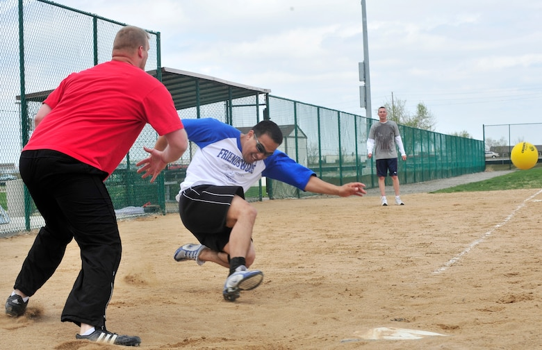 BUCKLEY AIR FORCE BASE, Colo. -- Danny Wong, 460th Medical Group, slides safely into home beating the throw during the Fitness Center's lunctime kickball tournament here April 30. Twelve teams participated in the tournament, where the 460th MDG won with a victory over the Marines in the championship game. The Fitness Center holds monthly lunchtime tournaments to promote physical fitness and esprit de coprs. For more information contact the Fitness Center at 720-847-6679. (U.S. Photo by Senior Airman Alex Gochnour)
