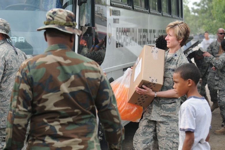 AZUA, Dominican Republic - U.S. Air Force Reserve Lt. Col. Carolyn Katrinchak works alongside Dominican Army troops, April 27, 2009, to unload medical supplies from a bus here. Col. Katrinchak, assigned to the 910th Medical Squadron, is participating in MEDRETE (Medical Readiness Exercise) designed to provide local residents with much needed medical care. (U.S. Air Force photo by Senior Airman Clinton Kline)