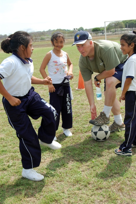 Maj. Brian Shumway, 478th Expeditionary Operations Squadron director of operations, teaches the basics of soccer to students from the Angelica Flores school at FOL Manta April 25. Volunteers from the FOL invited over 40 students to a sports day to learn American sports and build teamwork. (U.S. Air Force photo by 1st. Lt Beth Woodward)