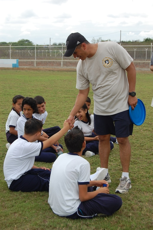 Master Sgt. Ben Miranda, 478th Expeditionary Operations Squadron chief of security forces and acting first sergeant, meets students from the Angelica Flores school at FOL Manta April 25. Volunteers from the FOL invited over 40 students to a sports day to learn American sports and build teamwork. (U.S. Air Force photo by 1st. Lt Beth Woodward)