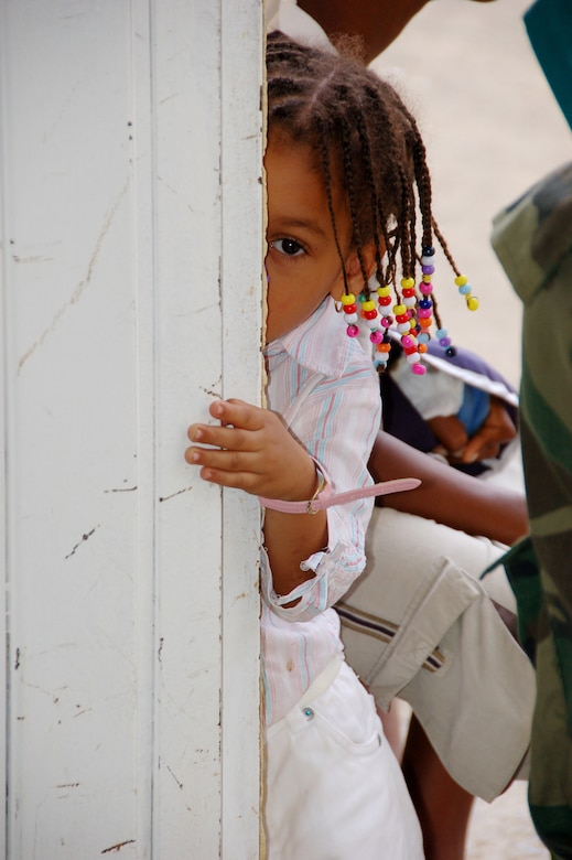 A small child cautiously peers into the pediatrician's room while awaiting her turn in line at a primary school turned temporary clinic in Hostos, Dom. Rep., April 22, during the largest Maxwell Air Force Base-planned U.S. Air Force Medical Readiness Training Exercise (MEDRETE) to date. A group of 45 medics, translators, security and support personnel derived from the U.S. Air Force, Army and Marines provided dental, dermatologic, general medicine, optometric, pediatric, pharmacy and public health services. The medics treated 2,800 patients during the first three days of the U.S. SOUTHCOM sponsored Beyond the Horizon 2009 – Caribbean. A MEDRETE is a U. S. Southern command-sponsored exercise designed to provide humanitarian assistance and free medical care to the people of the host nation, while providing an unparalleled training opportunity for U.S. and host nation forces. SOUTHCOM sponsors approximately 70 MEDRETEs per year. (U.S. Air Force Photo by Capt. Ben Sakrisson)