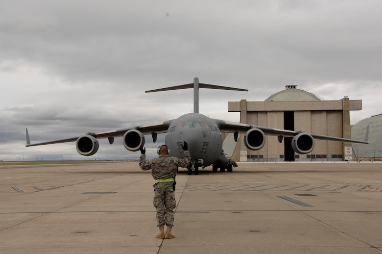 Tech Sgt. Fernando Wilkins, a 129th Maintenance Group crew chief, directs an incoming C-17 Globemaster to its parking spot at Moffett Federal Airfield, Calif.  The C-17 and its crews from McChord Air Force Base, Wash., arrived at Moffett to pick up passengers and equipment deploying to Afghanistan, May 3, 2009. (U.S. Air Force photo by Staff Sgt. Kim E. Ramirez)