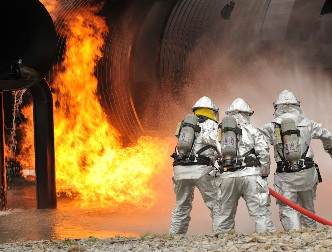 Firefighters attack the flames of a simulated aircraft fire during a joint training exercise May 4 at Offutt Air Force Base, Neb. Firefighters from active-duty, Air Guard and Reserve units participated in the joint training exercise for disaster preparation. (U.S. Air Force photo/Charles Haymond)