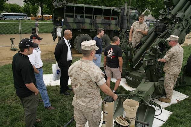 Cpl. Gavin Wageman and Staff Sgt. Raoul Sheridan talk about some of the M-777 Howitzer's capabilities during Public Service Recognition Week May 7.