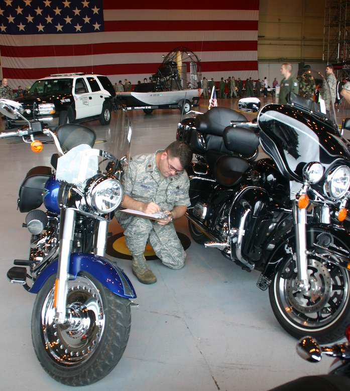Maj. Dwight Minnick, commander, 552nd Maintenance Operations Squadron, pays close attention to detail as he judges the motorcycles at the Safety & Wellness Fair May 8.