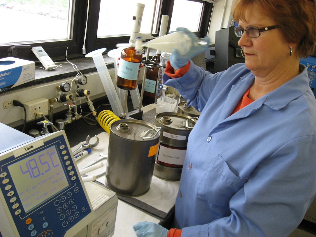 Janet Stewart concludes a test of the flash point temperature in a sample of commercial Jet A fuel while preparing to measure the concentration of fuel system icing inhibitor in another sample in the Aerospace Fuels Laboratory at Wright-Patterson Air Force Base, Ohio. Air Force Petroleum Agency and Air Force Research Laboratory researchers are partnering on an initiative to evaluate the use of commercial jet fuel in place of military standard JP-8 fuel. Ms. Stewart is a fuels quality assurance specialist with the Aerospace Fuels Laboratory at Wright-Patterson AFB. (U.S. Air Force photo/Derek Kaufman)