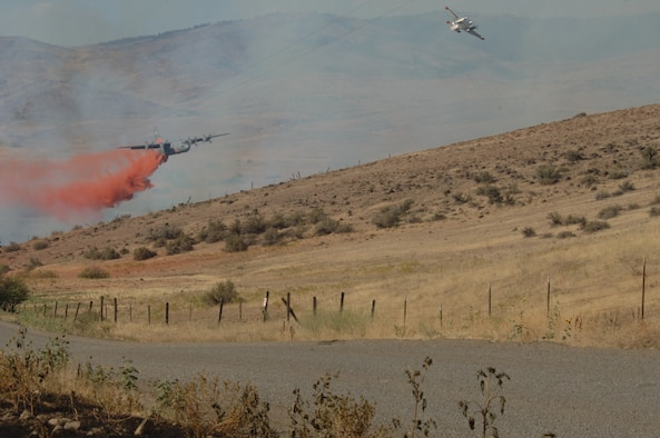 A C-130 uses aerial firefighting equipment known as the Modular Airborne Fire Fighting System to drop red-colored retardant, or 'slurry' as it is sometimes called, from the plane into the air over a fire. MAFFS was established by Congress in the early 1970s to create a national response system to better fight major fires. (U.S. Air Force Photo)