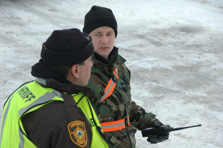 2nd Lt. Jeffery Hovdeness, of the 119th Wing, leads a quick response force team as he discusses plans for civilian welfare visits in rural areas north of Fargo with a Cass County Sherrif's deputy April 1.