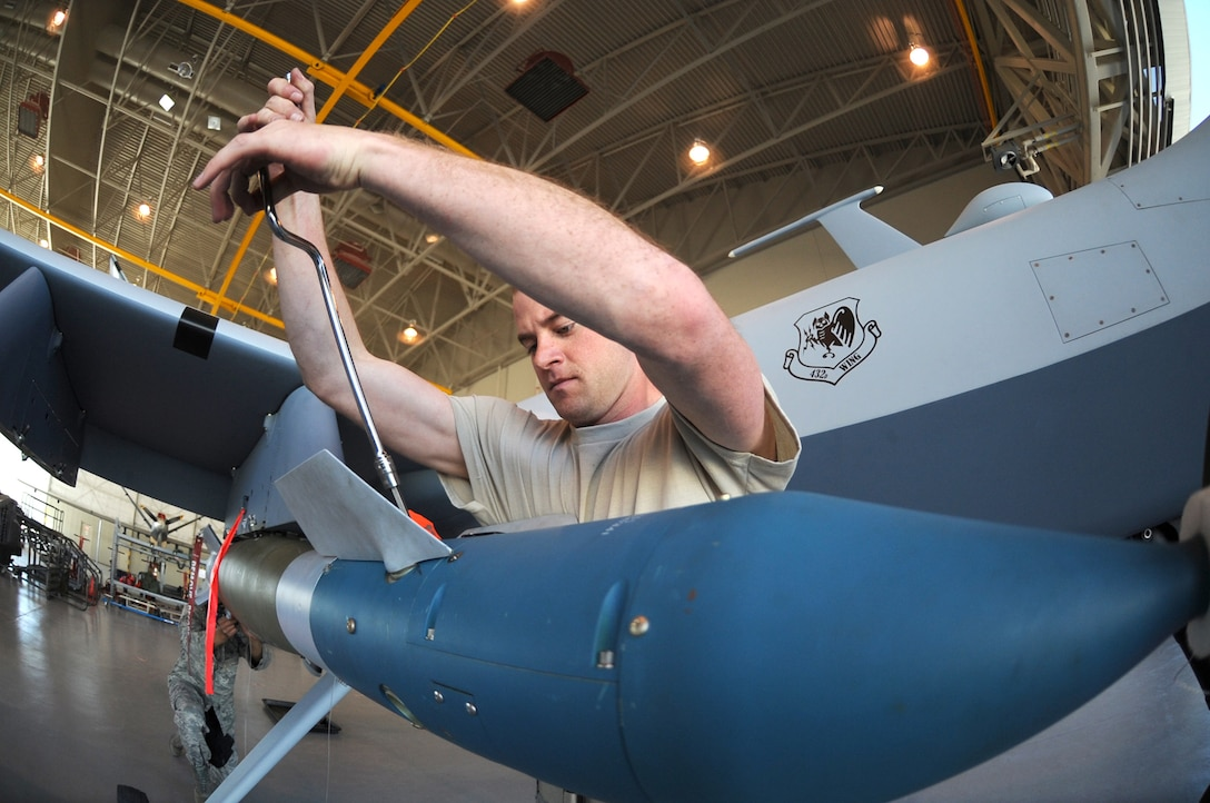 Senior Airman Jason Atwell secures the fins onto a guided bomb unit-12 Paveway II laser-guided bomb during weapons load training April 22 at Creech Air Force Base, Nev. MQ-9 Reaper load crew members were conducting monthly training to maintain their qualifications on the airframe. Airman Atwell is a MQ-9 Reaper weapons loader assigned to the 432nd Aircraft Maintenance Squadron.  (U.S. Air Force photo/Senior Airman Larry E. Reid Jr.)