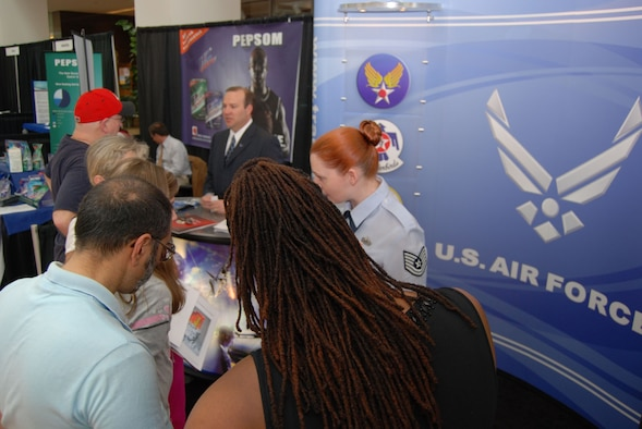 ALEXANDRIA, Va. - Mr. Richard Osburn and Tech. Sgt. Jennifer Buzanowski, Air Force Public Affairs Agency, talk to visitors of the U.S. Patent and Trademark Office's 2009 Expo May 9. The Air Force Trademark and Licensing Office was the first military branch to attend the USPTO's annual expo that drew a crowd of 7,000 people for the two-day event. The U.S. Air Force Band performed during the opening ceremony May 8. (U.S. Air Force Photo/Jessica O'Haver)