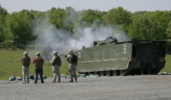 Personnel from the Expeditionary Fighting Vehicle Program Office stand next to an EFV as it fires 30 mm rounds from its MK44 Bushmaster automatic cannon during a testing evolution May 12.