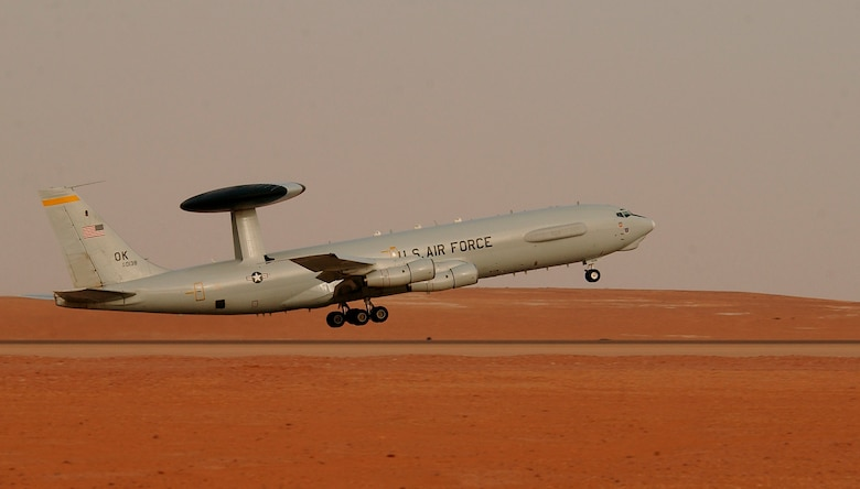 An E-3 Senty AWACS takes off in the desert.