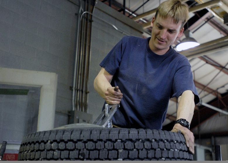 ELMENDORF AIR FORCE BASE, Alaska -- Robert Nelson mounts one of his new summer tires onto a rim in the process of switching out his winter tires for a new summer set. Nelson is a Major for the 210th Reserve Alaska Guard.(U.S. Air Force photo/Airman 1st Class Christopher Gross)