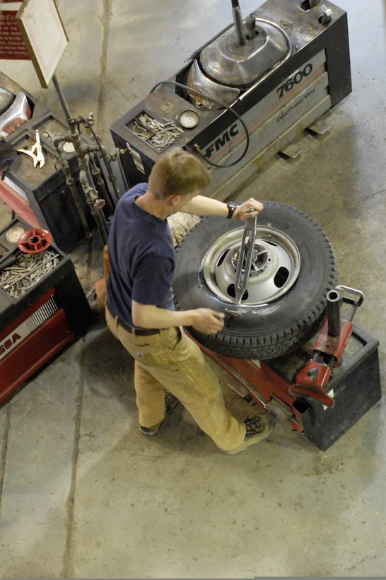 ELMENDORF AIR FORCE BASE, Alaska -- Robert Nelson demounts one of his winter tires in the process of changing his winter set of tires to a new summer set, May 8. Melson is a major with the 210th Reserve Alaska Guard.(U.S. Air Force photo/Airman 1st Class Christopher Gross)