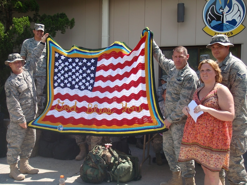 Lt. Col. Douglas Hagen, commander, 728 ACS, accepts on behalf of the squadron a homemade blanket as a departing gift from a local church that one of the deploying Airmen attends. (U.S. Air Force photo/Senior Airman Rachel Chapman)