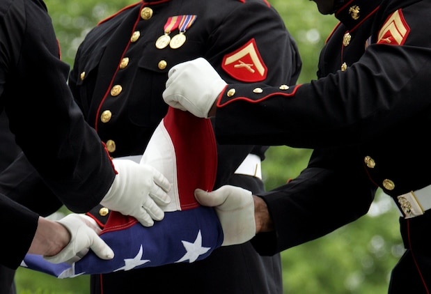 Casket bearers fold the burial flag during a group repatriation service May14. A throng of family members and Marine veterans gathered to remember the service and sacrifice of six Vietnam War casualties whose remains had recently been identified and repatriated.