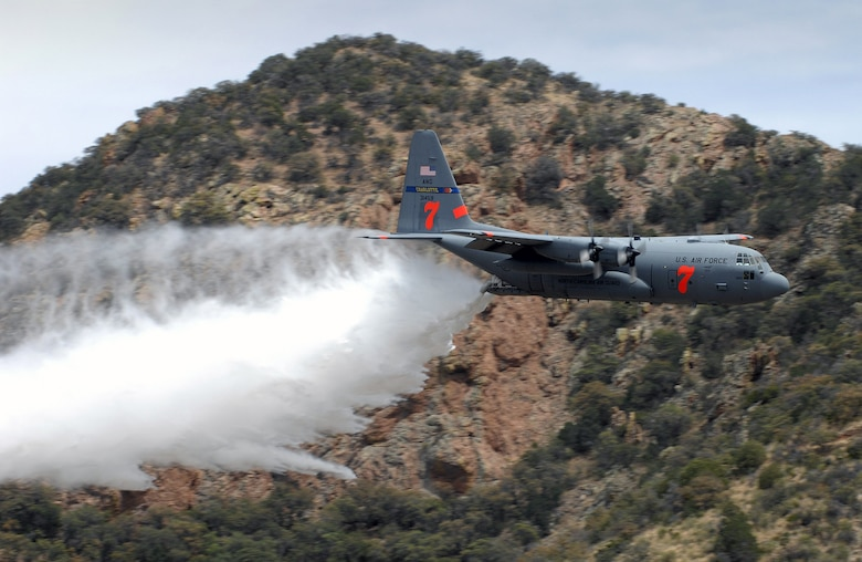 """A C-130 Hercules drops """"fire retardant"""" from a Modular Airborne Fire Fighting System near Tucson, Ariz., May 8 to finalize MAFFS certification by the U.S. Forestry Service.  Air Force Reserve and Air National Guard aircrews flew training missions from sun up to sundown in the annual event. (U.S. Air Force photo/Tech. Sgt. Alex Koenig)"""