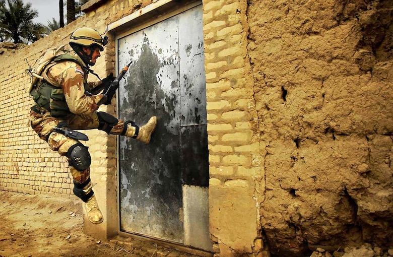 The Stacy Pearsall Combat Photo Gallery — A Military Photographer of the Year, Pearsall's work has been viewed worldwide. An Iraqi army soldier tries to kick open a gate during a cordon and search for insurgence and weapons caches in Chubinait, Iraq, on Feb. 3, 2007. (photo by Staff Sgt. Stacy Pearsall)