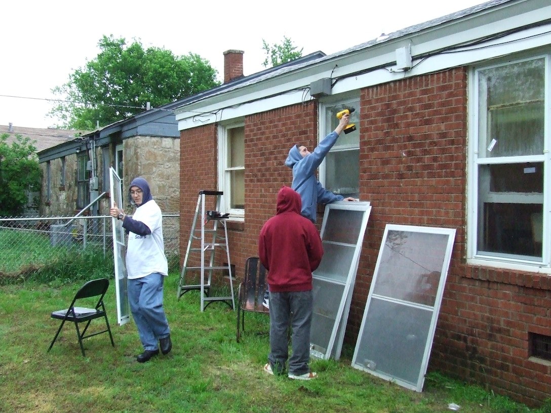 Members of the 552nd Air Control Networks Squadron install new storm windows on the Lamberts' home as part of the Rebuilding Together community service project. (US Air Force Photo courtesy of Airman First Class Taj V. Preciado)