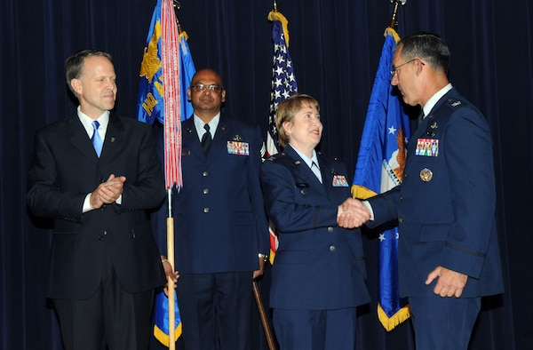 Col. Frederic Ryder (right) congratulates Col. Sandra Adams, the Air Force Services Agency's new commander, after a change-of-command ceremony May 12 at Randolph Air Force Base, Texas.  Colonel Adams succeeded Colonel Ryder who was honored in a retirement ceremony earlier that day.  The change of command, which featured performances by Tops in Blue vocalists, included remarks by Charles Milam (left), Air Force Services director. (U.S. Air Force photo/Joel Martinez)