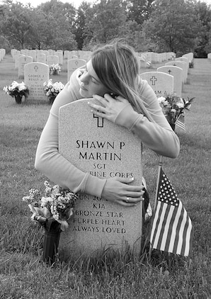 Mimi Martin embraces her husband's grave marker during a recent visit. Her husband, Sgt. Shawn P. Martin, an explosive ordnance disposal technician, was killed in action June 20, 2007. As the two-year mark of her husband's death approaches, Martin carries on her husband's legacy daily with her work as the spokeswoman for the New York State Fallen Stars Memorial Project.