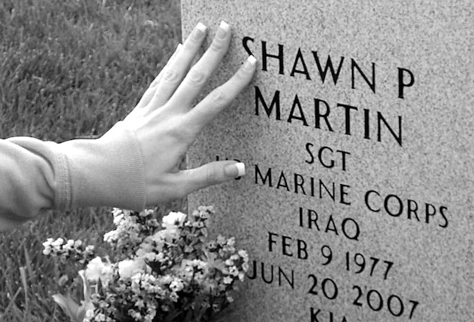 Mimi Martin, a military widow, touches her husband's name during a recent visit to his final resting place. Her husband, Sgt. Shawn P. Martin, an explosive ordnance disposal technician, was killed in action June 20, 2007. As the two-year mark of her husband's death approaches, Martin carries on her husband's legacy daily with her work as the spokeswoman for the New York State Fallen Stars Memorial Project.