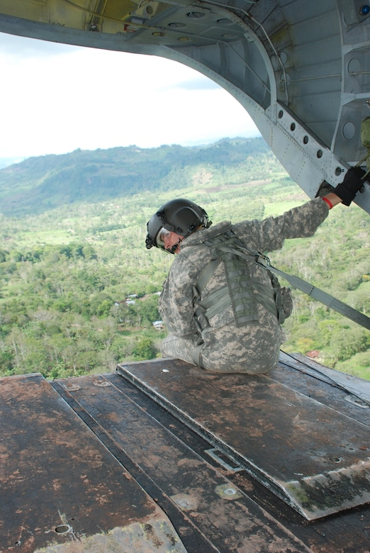 Army Sgt. Michael Marquis, 1st Battalion, 228th Aviation Regiment, keeps a watchful eye out the rear of his aircraft during flight.  He is looking for any hazards that might come within range of the 32,000-pound aircraft.  Sergeant Marquis is a CH-47D Chinook crew chief assigned to the Joint Task Force-Bravo Chinook crew in Nicaragua this week to fly medics and equiment to two remote villages for medical readiness exercises.  (U.S. Air Force photo/Tech. Sgt. Rebecca Danét)
