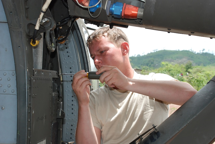 Army Sgt. Danny Hewett, 1st Battalion, 228th Aviation Regiment, inspects the main landing gear of his UH-60 Blackhawk during a 40-hour inspection May 15.  Sergeant Hewett is a Blackhawk crew chief assigned to one of two Joint Task Force-Bravo Blackhawk crews in Nicaragua this week to fly medics and equiment to two remote villages for medical readiness exercises.  (U.S. Air Force photo/Tech. Sgt. Rebecca Danét)
