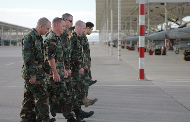 Members of the 162nd Maintenance Group propulsion section gather for a morning FOD walk on the flightline at Tucson International Airport. Members line up daily and walk in search of foreign object damage that can cause harm to aircraft. (Air National Guard photo by Tech. Sgt. Desiree Twombly)