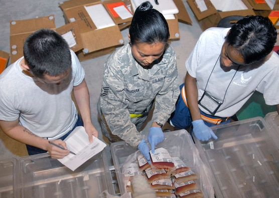 Tech. Sgt. Marilou Vaughan (center), a 379th Expeditionary Medical Group Blood Transshipment Center lab technician, shows Staff Sgt. Anthony Bradford and 1st Lt. Jacquelyn Smith, both volunteers from the 379th EMDG at this air base in Southwest Asia, where to find the unit number on frozen blood units here May 9. The BTC staff uses base volunteers to assist in checking incoming blood product packaging for damage before the products are distributed throughout the U.S. Central Command area of responsibility. (U.S. Air Force photo/Senior Airman Andrew Satran)