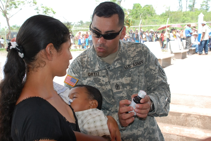 Army 1st Sgt. Jorge Ortiz, of Joint Task Force-Bravo's Army Forces, explains the directions of a pharmacy technician to a woman seen during the task force's medical readiness exercise here May 14 and 15.  Thirty-four Soldiers and Airmen participated in the exercise, including aviators, doctors, nurses, technicians, translators and administrators.  (U.S. Air Force photo/Tech. Sgt. Rebecca Danét)