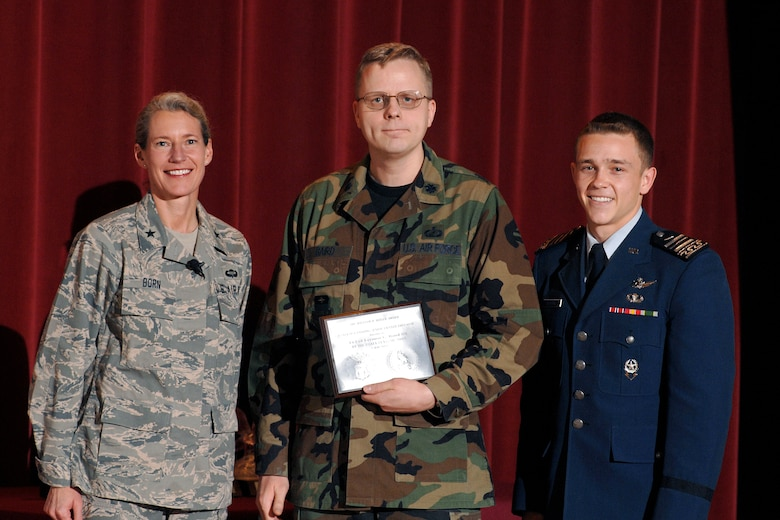 Lt. Col. Leemon Baird, center, receives a 2009 Heiser Award from Brig. Gen. Dana Born, dean of the faculty, and Cadet 1st Class Jacob Schonig, Fall 2008 cadet wing commander, during an award presentation May 7. Each graduating class selects two senior faculty members from more than 160 eligible professors to receive the award. (U.S. Air Force photo/Dennis Rogers)