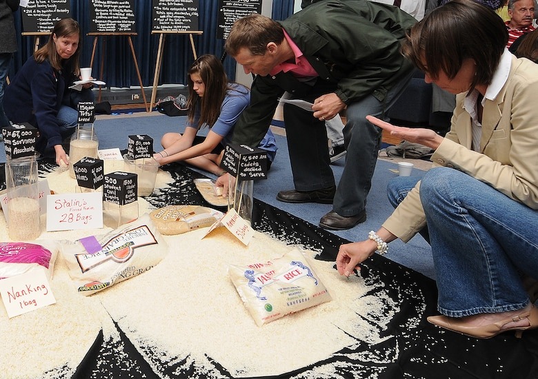 """Members of the Air Force Academy community received a unique history lesson during a Holocaust remembrance gathering April 30 in the Arnold Hall Ballroom. The """"rice project"""" included a teacher pouring rice into different piles on the floor; each pile represented a different genocide, and the grains of rice represented lives lost in each of the tragedies. (U.S. Air Force photo/Rachel Boettcher)"""