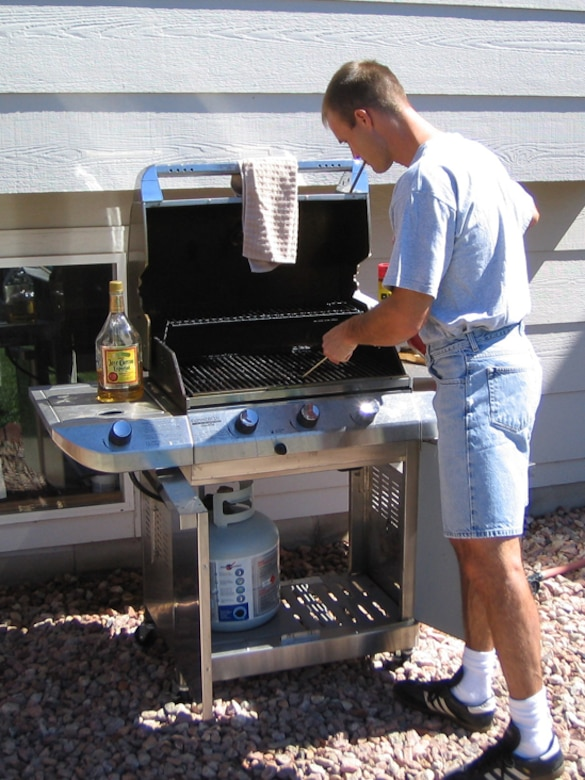 While barbecues provide a fun and casual dining experience, they also provide the ideal conditions for a costly mishap. Keep the grill off wooden decks and away from children's play areas and low-hanging tree branches. (U.S. Air Force file photo)