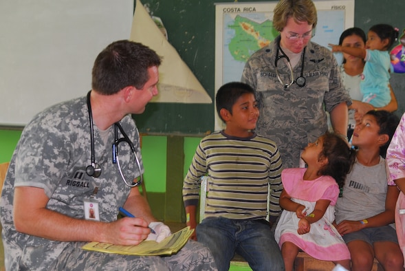 ALAJUELA, Costa Rica -- Capt. Michael Riggall, a 30th Medical Group pediatrician, and Lt. Col. Stephanie Schaefer, a physician from Lackland Air Force Base, Texas, provide medical care to local children here May 19. A team of Air Force medical specialists is participating in a joint humanitarian mission with local physicians of Costa Rica. (U.S. Air Force/Airman 1st Class Steve Bauer)