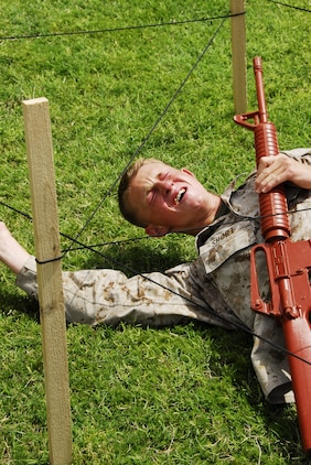 Cpl. Stolf Short, a Marine Corps Air Station Yuma, Ariz. Search and Rescue maintenance administrator, crawls under simulated barbed wire after being sprayed with Oleoresin Capsicum during a martial arts instructor course May 21, 2009.(Photo by Cpl. Laura A. Mapes)