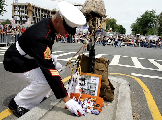Staff Sgt. Tim Chambers places a display donated by a 'Gold Star' family at the foot of his makeshift memorial to the fallen of Iraqi and Afghanistan May 24. He stood at the memorial for three hours saluting veterans as they passed on motorcycles during the 22nd annual Rolling Thunder.