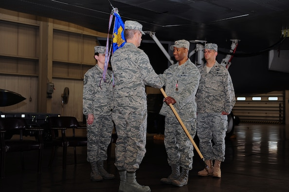 Maj. Michael Edwards, outgoing 28th Maintenance Operations Squadron commander, hands the guidon to Col. Thomas Fitch, 28th Maintenance Group commander, during a change of command ceremony here, May 21. By handing the guidon off, Major Edwards relinquishes command of the 28 MOS. (U.S. Air Force photo/Airman 1st Class Joshua Seybert)