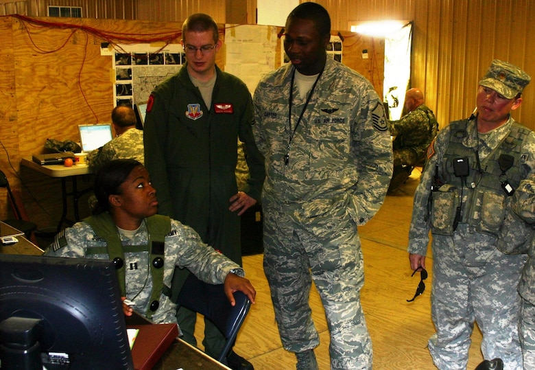 Army Capt. Lacey Johnson, collection manger, 1st BCT, 82nd (left); Air Force 1st Lt. Kurtis Kuschel, JSTARS liaison officer; Air Force Master Sgt. Ronnie Carter, JFIIT JSTARS subject matter expert; and Army Maj. Typhanie Montemayor, senior military intelligence company training mentor, JRTC discuss the BCT's collection plan during JRTC rotation 09-06.  (Photo: Casey Bain, JFIIT, USJFCOM)