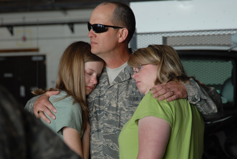 Master Sergeant Doug Nicholson, spends a few quiet moments with his wife, Julie and daugther, Sammantha, before departing Buckley Air Force Base for a six-month deployment to the U.S. Central Command Area of Operations.