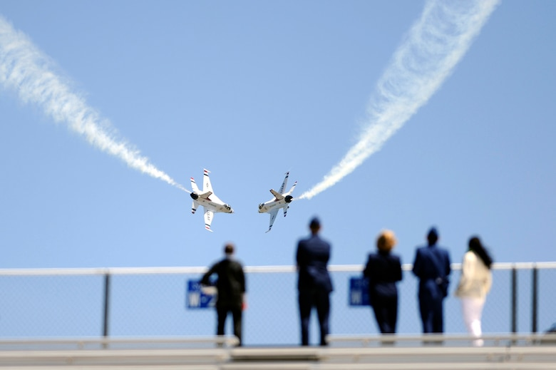 Two Air Force Thunderbirds execute a maneuver over the U.S. Air Force Academy's Falcon Stadium May 27 following the graduation of the Class of 2009.  This was the 51st graduating class where 1,046 cadets were commissioned as second lieutenants.  Vice President Joe Biden was the commencement speaker.  (U.S. Air Force photo/Dennis Rogers)