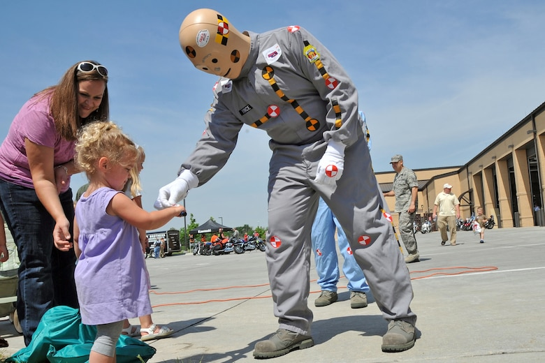 OFFUTT AIR FORCE BASE, Neb. -- Nora Panter, age 2, daughter of Holly Panter and Maj Jake  Panter, 55th Wing, receives a sticker from a crash test dummy, while her mother looks on during a safety fair at the Offutt Fire House May 21. Safety fair patrons enjoyed numerous activities including a seat-belt simulator and a motorcycle-show-and-shine. The safety fair was part of Offutt's annual Safety Day, which focuses on reminding all Airmen to practice safety on a daily basis. U.S. Air Force Photo by Jeff W. Gates