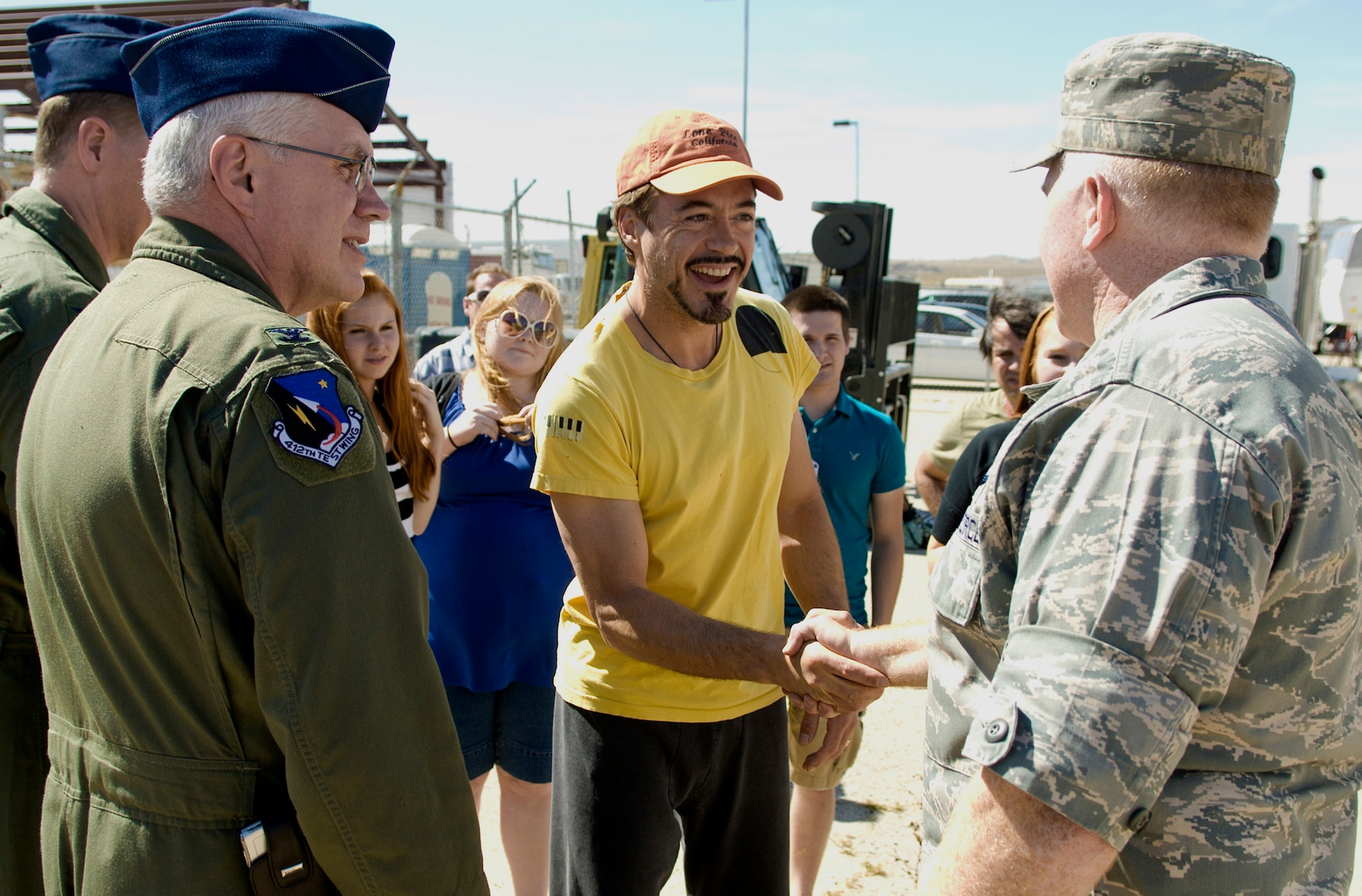 """""""Ironman II"""" actor Robert Downey Jr. (center) shakes hands with Col. Jerry Gandy (right) during a break in filming here May 13 at Edwards Air Force Base, Calif. About 60 members of Edwards AFB participated in the filming as extras and technical advisers. Colonel Gandy is the 95th Air Base Wing commander. (U.S. Air Force photo/Mike Cassidy)"""