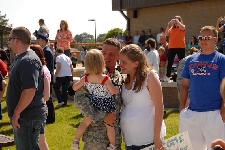 Kansas Air Guard's 134 Air Control Squadron member, TSgt Justin Moody, gets hugs and kisses from his daughter and wife at the re-deployment ceremony welcoming his unit home from their deployment to Iraq.