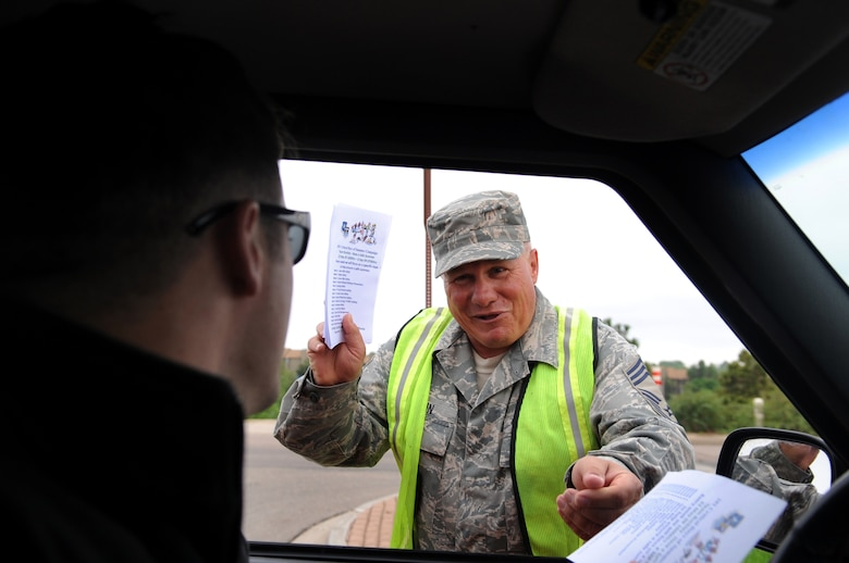 BUCKLEY AIR FORCE BASE, Colo. -- Kicking off the 101 Critical Days of Summer, Chief Master Sgt. James Martin, 460th Civil Engineer Squadron, hands out flyers to members of Buckley as they enter the base. The 101 Critical Days of Summer campaign runs through Labor Day and helps raise awareness for on- and off-duty activities during the summer months. (U.S. Air Force photo by Senior Airman Erika Brooke)